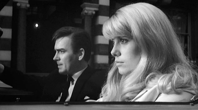Colin (gespielt von John Fraser) und Carol (gespielt von Catherine Deneuve) sitzen in Colins geparktem Roadster