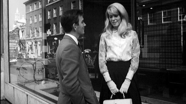 Colin (gespielt von John Fraser) und Carol (gespielt von Catherine Deneuve) stehen vor dem Schaufenster eines Geschäfts