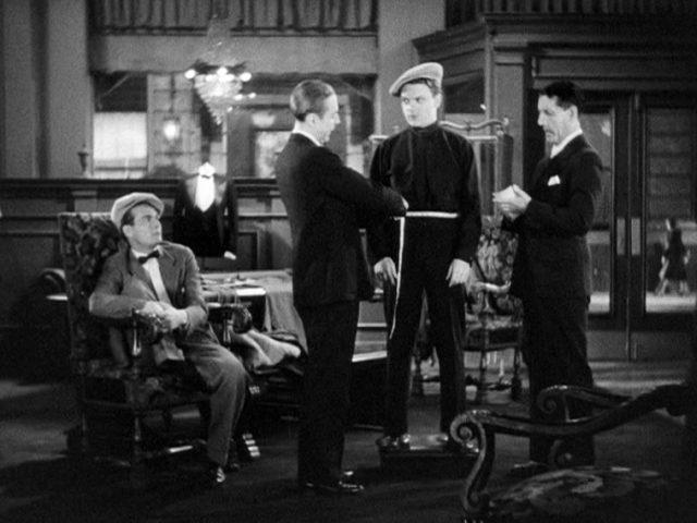 Tom Powers (gespielt von James Cagney) steht auf einem Podest in der Mitte eines Schneidergeschäfts und lässt sich mit skeptischem Blick von einem Angestellten mit einem Maßband ausmessen, Copyright: Turner Entertainment