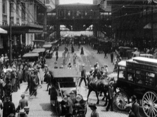 Blick in den Trubel einer innerstädtischen Straße, auf der neben Passanten sowohl eine Pferdekutsche als auch Automobile zu sehen sind