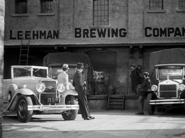 Gangster warten mit ihren Fahrzeugen vor einem Brauereigebäude