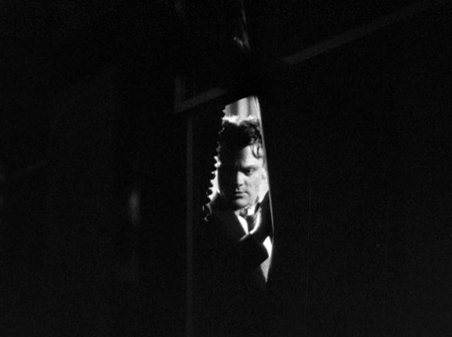 durch einen Spalt erkennbarer Tom Powers in einem ansonsten dunklen Bild