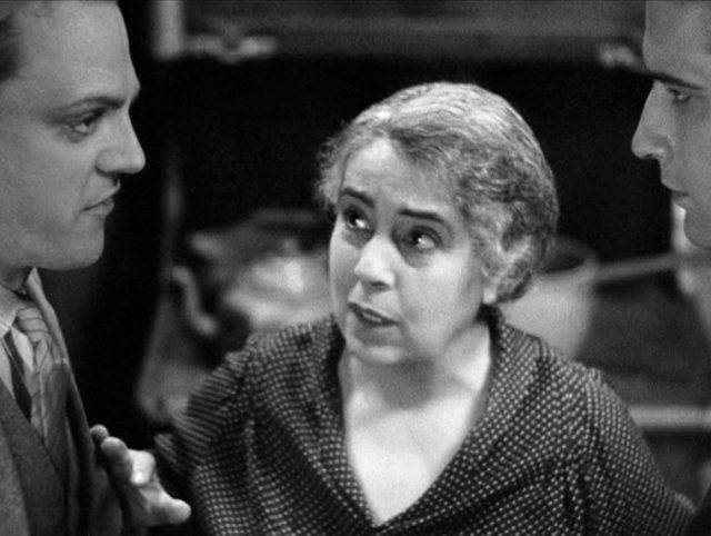 Ma Powers (gespielt von Beryl Mercer) steht symbolisch zwischen ihren beiden Söhnen Tom und Mike