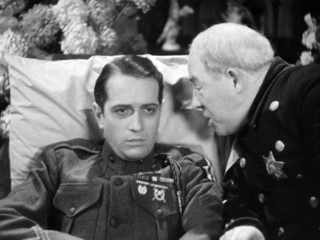 Mike Powers (gespielt von Donald Cook) in der Uniform eines US-Soldaten im Gespräch mit seinem Vater (gespielt von Purnell Pratt) in der Uniform eines Polizisten