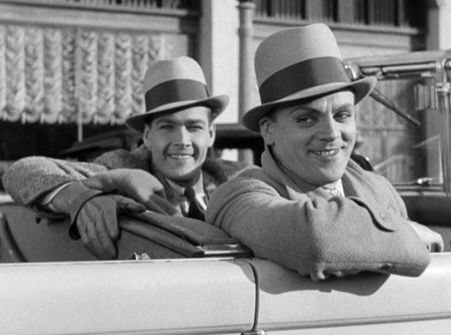 Matt Doyle (gespielt von Edward Woods) und Tom Powers (gespielt von James Cagney) sitzen grinsend in ihrem Cabrio