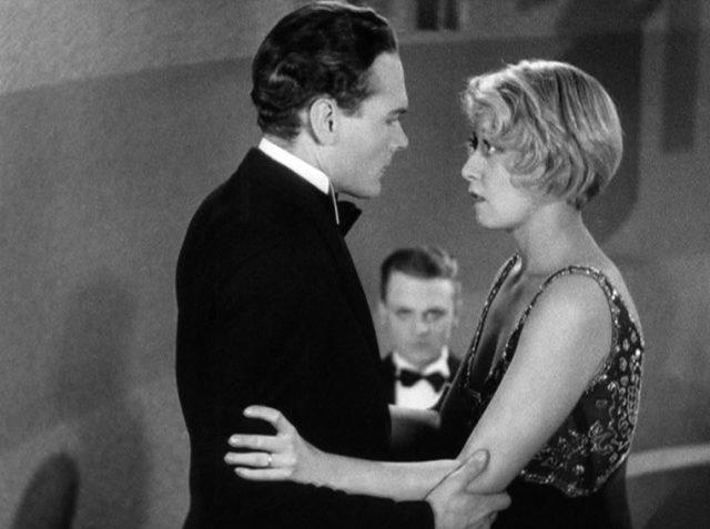 Matt Doyle (gespielt von Edward Woods) und Mamie (gespielt von Joan Blondell) sind beide in Abendgarderobe gekleidet und blicken sich an; im Hintergrund ist James Cagney als Tom Powers mit auf die beiden gerichtetem Blick zu erkennen, Copyright: Turner Entertainment
