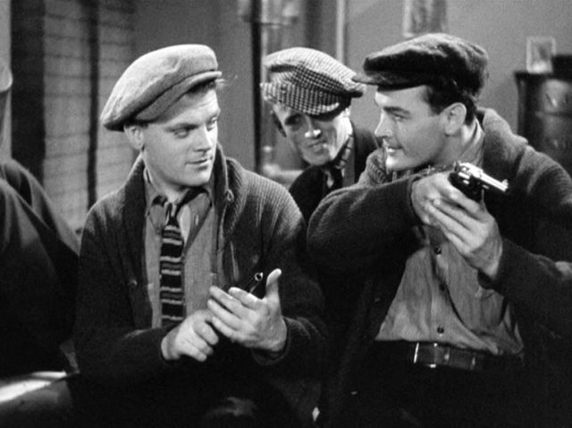 Tom Powers (gespielt von James Cagney) und Matt Doyle (gespielt von Edward Woods) blicken sich in die Augen, während sie ihre neuen Revolver in Händen halten