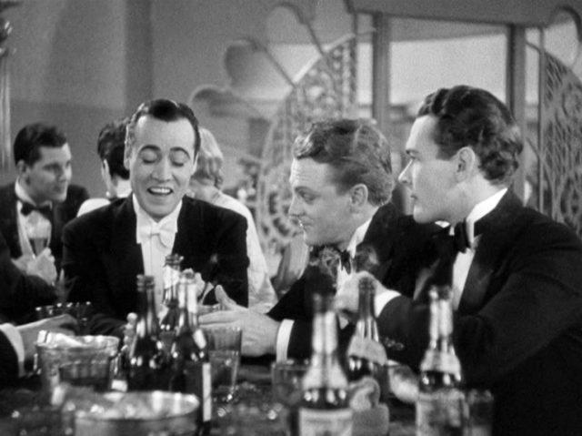 die Gangster Nathan (gespielt von Leslie Fenton), Powers (gespielt von James Cagney) und Doyle (gespielt von Edward Woods) sitzen in einer Bar in Gegenwart etlicher Getränke