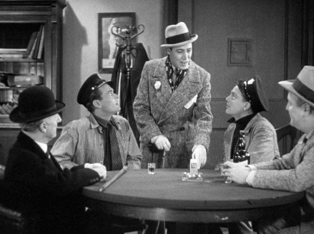 """Samuel """"Nails"""" Nathan (gespielt von Leslie Fenton) steht an einem runden Tisch, an dem vier Gangster sitzen, unter ihnen Matt Doyle (gespielt von Edward Woods) und Tom Powers (gespielt von James Cagney)"""