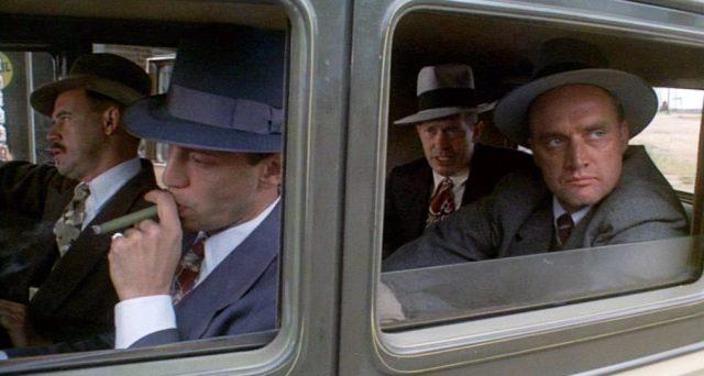 Dillinger und drei seiner Komplizen warten im Innern ihrer Limousine, der Fahrer zieht an seiner Zigarre.