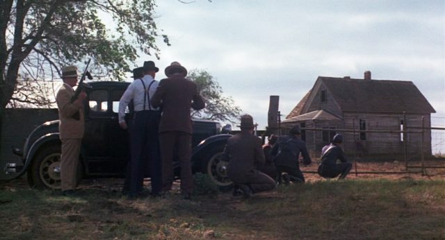 FBI-Agenten belagern im Schutz eines Fahrzeugs schwer bewaffnet ein einzelnes Holzhaus.