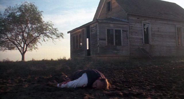Die Leiche eines erschossenen Gangsters liegt im Matsch vor einem maroden Holzhaus.