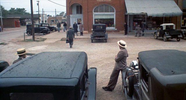 Mit bereitstehenden Limousinen warten die Gangster vor einer kleinen Bank.