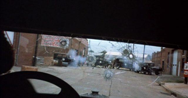 """Innenperspektive eines Fluchtfahrzeuges der """"Dillinger Gang"""", das auf eine Polizeisperre zurast und in der Windschutzscheibe bereits mehrere Einschusslöcher aufweist."""