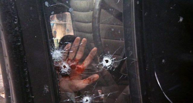"""Eine blutverschmierte Hand berührt die mit Einschusslöchern gespickte Windschutzscheibe eines havarierten Fluchtfahrzeugs der """"Dillinger Gang""""."""