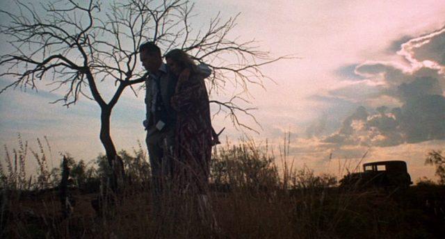 Dillinger und seine Freundin stehen in der Abenddämmerung am Grab des verstorbenen Mackley.