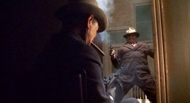 Purvis, mit Zigarre im Mund, erschießt einen Gangster, der im Türrahmen steht, mit seiner Maschinenpistole.