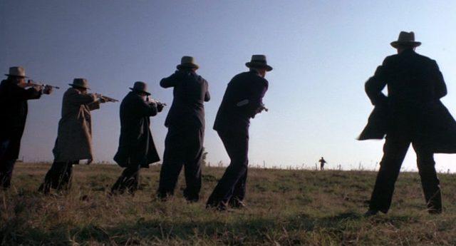 Eine Reihe von FBI-Agenten steht auf einem Feld und zielt auf einen flüchtenden Gangster.