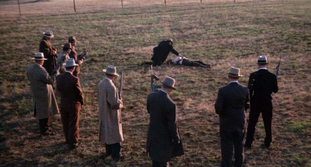 FBI-Agenten stehen auf einem Feld im Halbkreis um die Leiche eines erschossenen Gangsters, neben der Purvis kniet.
