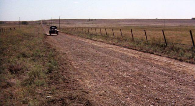 Eine Limousine fährt eine staubige Straße im Mittleren Westen entlang.