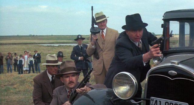 FBI-Agenten haben sich mit ihren Waffen hinter einem Fahrzeug verschanzt, im Hintergrund stehen Schaulistige.