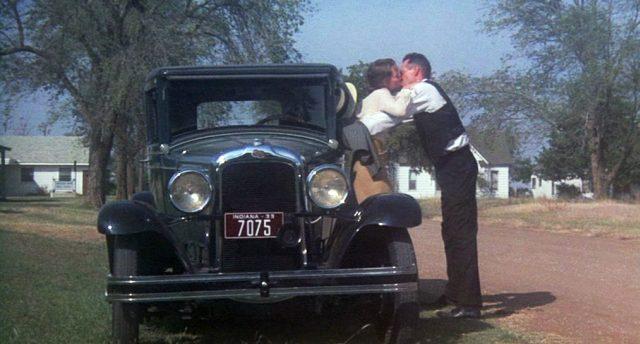 Dillinger küsst seine Freundin, die an der Karosserie von Dillingers Limousine auf einer Straße in einer Kleinstadt lehnt.
