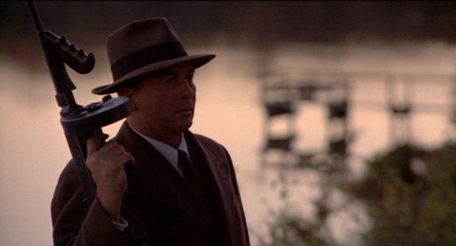 Ein dunkel ausgeleuchteter FBI-Agent steht mit erhobener Maschinenpistole in der Dämmerung.