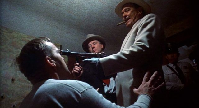 Melvin Purvis (gespielt von Ben Johnson) bedroht einen gestellten Gangster mit seiner Maschinenpistole im Beisein eines weiteren FBI-Agenten.