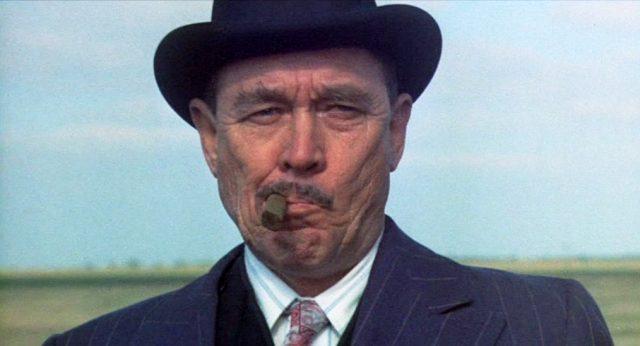 Nahaufnahme von Ben Johnson als Melvin Purvis mit Zigarre im Mundwinkel auf einem Feld irgendwo im Mittleren Westen.