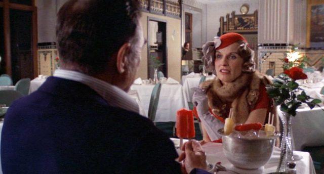 Cloris Lechman als Anna Sage am Tisch in einem luxuriösen Restaurant im Gespräch mit Melvin Purvis, der mit dem Rücken zur Kamera sitzt und ein Eis am Stiel hält., Copyright: Orion Pictures