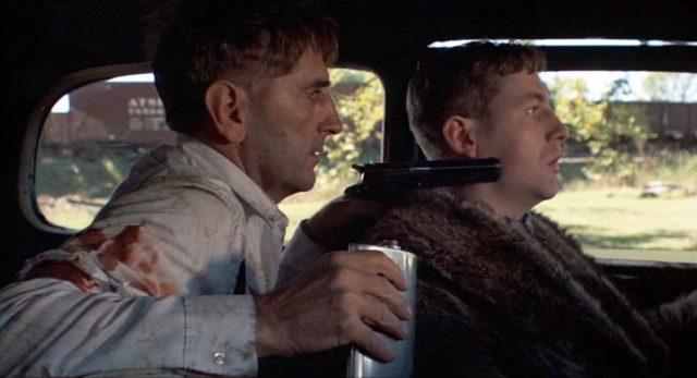 Homer Van Meter (gespielt von Harry Dean Stanton) bedroht von der Rückbank einer Limousine aus den Fahrer des Wagens mit seiner Pistole.