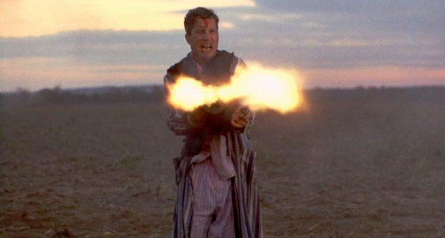Richard Dreyfuss steht als Baby Face Nelson auf einem Feld und feuert seine Maschinenpistole ab; das infernalische Mündungsfeuer ist zu sehen.