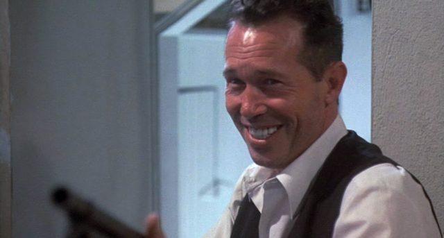 Warren Oates als lächelnder John Dillinger mit Shotgun.