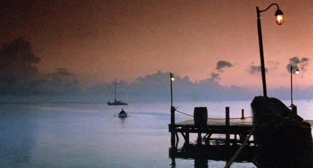 idyllische Szenerie, im Vordergrund ein Bootssteg, im Hintergrund rudert jemand in einem kleinen Boot zu einer ankernden Jacht