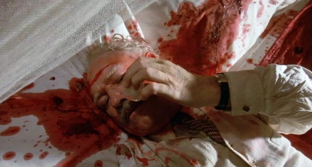 Gene Hackman als Jack McCann, der halbtot und blutverschmiert auf seinem Bett liegt, Copyright: Sunley Prod. Ltd.