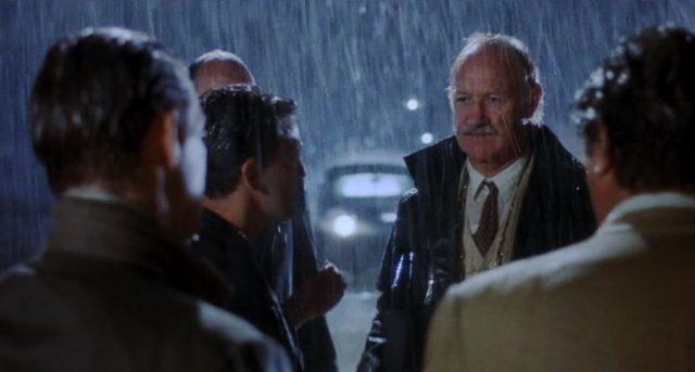 Jack McCann (gespielt von Gene Hackman) steht nachts im starken Regen vor einer Gruppe Gangster, Copyright: Sunley Prod. Ltd.