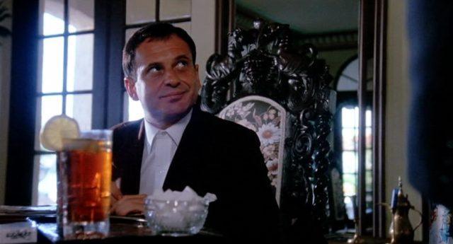 Joe Pesci als Gangsterboss Mayakofsky in dessen Villa am Esstisch mit einem Cocktail, Copyright: Sunley Prod. Ltd.