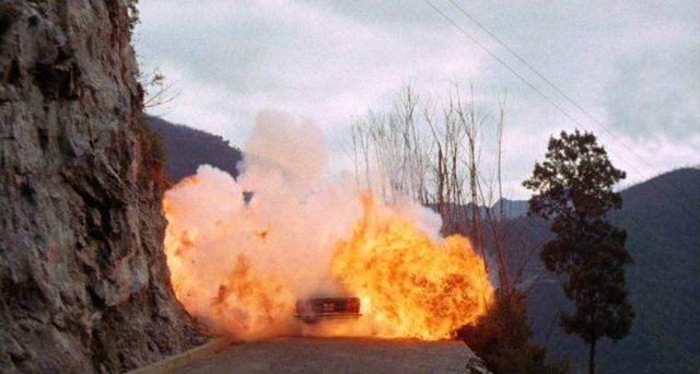 explodierendes Fahrzeug auf einer engen Straße an einer Felswand