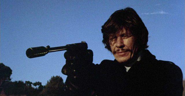 Arthur Bishop (gespielt von Charles Bronson) zielt mit einer schallgedämpften Pistole aus einem Hinterhalt