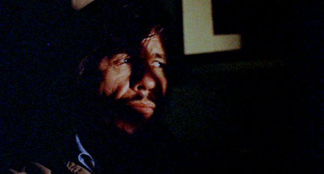 Nahaufnahme von Arthur Bishop (gespielt von Charles Bronson) in einem Appartement, auf seinem Gesicht liegen Schatten