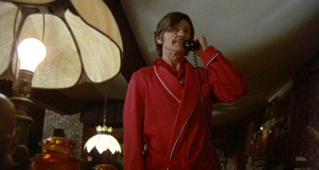 Arthur Bishop (gespielt von Charles Bronson) steht in einem roten Morgenmantel mit dem Telefonhörer am Ohr in seiner Wohnung
