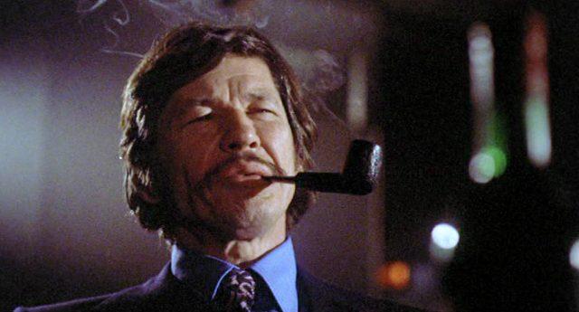 Nahaufnahme von Arthur Bishop (gespielt von Charles Bronson) mit einer Pfeife im Mund