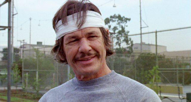 Nahaufnahme von Arthur Bishop (gespielt von Charles Bronson) in grauem Trainingsoutfit mit Stirnband