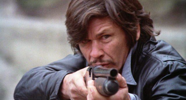 Nahaufnahme von Arthur Bishop (gespielt von Charles Bronson) in Lederjacke mit einer Shotgun im Anschlag und konzentriertem Blick
