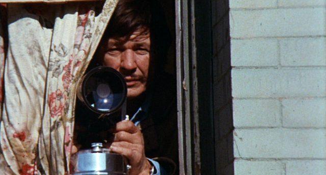 Arthur Bishop (gespielt von Charles Bronson) beobachtet vorsichtig aus einem Fenster heraus