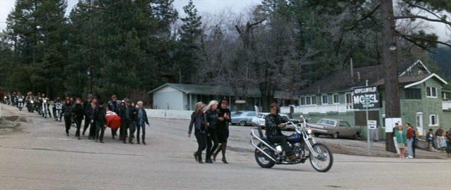 Die Motorradgang zieht als Trauerprozession durch einen kleinen Ort; voran fährt Heavenly Blues mit seiner Maschine, hinter ihm trägt eine Gruppe zu Fuß den Sarg, im Hintergrund rollen weitere Motorräder.