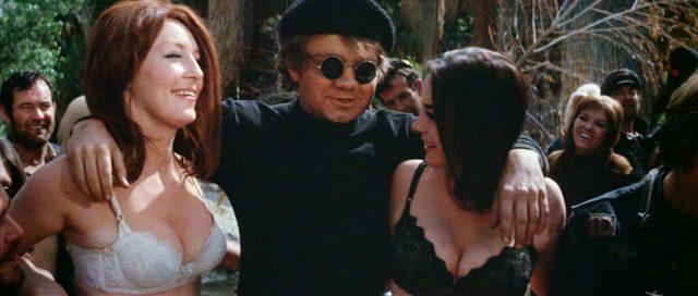 Mitglieder der Gang in einem kleinen Waldstück, im Vordergrund steht ein Mann zwischen zwei Frauen, die am Oberkörper lediglich einen BH tragen.