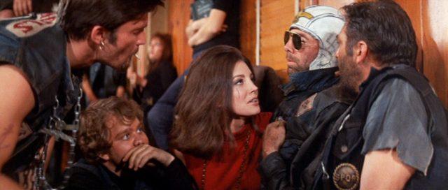 Mitglieder der Gang haben die Leiche ihres Kumpels Loser (gespielt von Bruce Dern) an der Wand einer Kirche drapiert und ihr eine Sonnenbrille aufgezogen.