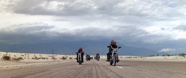 Die Kamera filmt auf Höhe der Fahrbahn die in einer Zweierreihe herannahenden Motorräder der Gang.