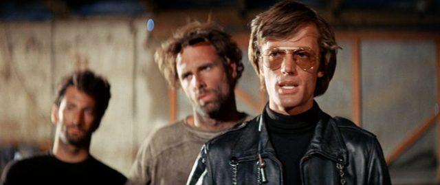 Loser (gespielt von Bruce Dern) und Heavenly Blues (gespielt von Peter Fonda) stehen in einem Raum, im Hintergrund ist verschwommen ein drittes Gangmitglied zu erkennen., Copyright: Orion